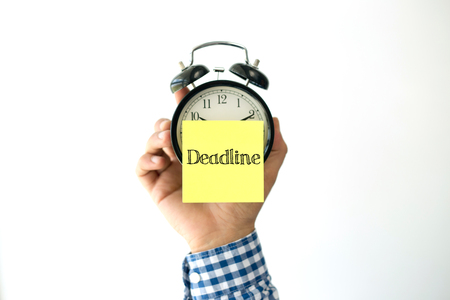 lateness: Hand Holding Alarm Clock and Pointing DEADLINE