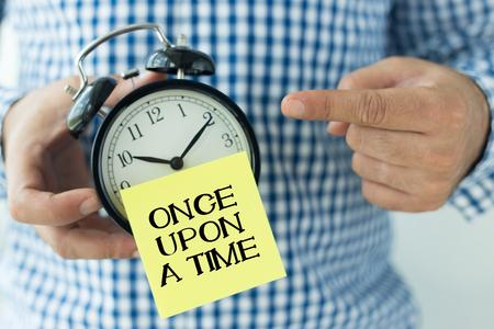 suspenso: Mano que sostiene la alarma del reloj y que señala ERASE UNA VEZ Foto de archivo