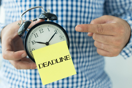 tardiness: Hand Holding Alarm Clock and Pointing DEADLINE