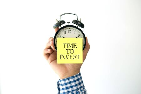 property management: Hand Holding Alarm Clock and Pointing TIME TO INVEST Stock Photo