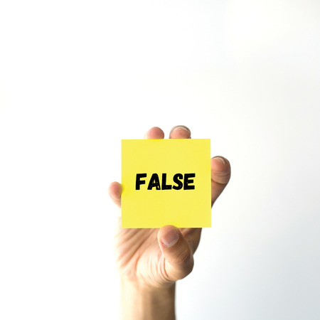 dishonesty: Hand holding yellow sticky note written False word