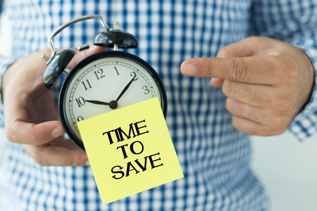 frugality: Hand Holding Alarm Clock and Pointing TIME TO SAVE