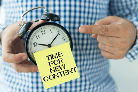 keywords link: Hand Holding Alarm Clock and Pointing TIME FOR NEW CONTENT