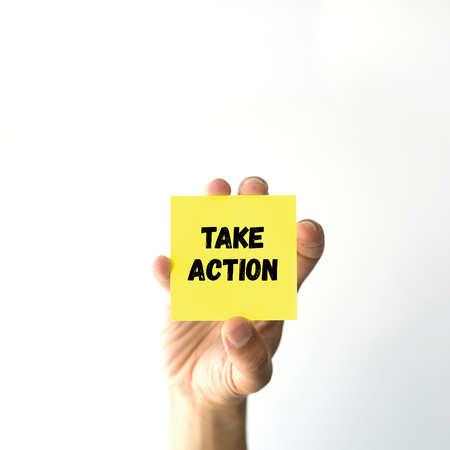 take a note: Hand holding yellow sticky note written TAKE ACTION word