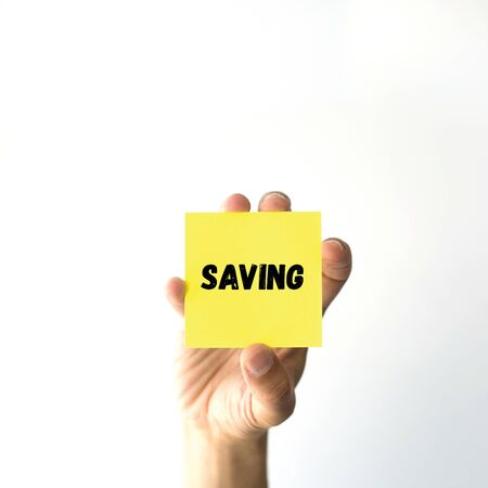 frugality: Hand holding yellow sticky note written SAVING word