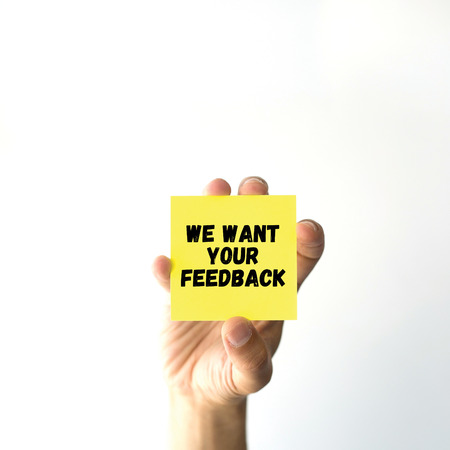 want: Hand holding yellow sticky note written WE WANT YOUR FEEDBACK