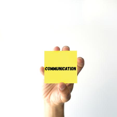 comunicaci�n escrita: Mano que sostiene la nota amarilla pegajosa palabra escrita COMUNICACI�N Foto de archivo