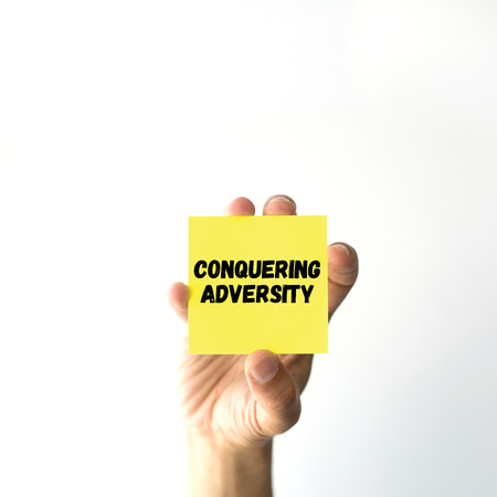 adversity: Hand holding yellow sticky note written CONQUERING ADVERSITY