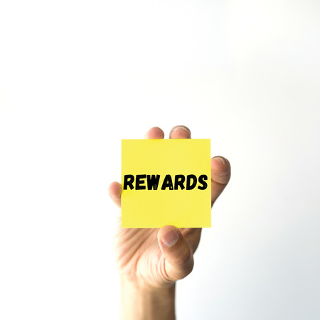payoff: Hand holding yellow sticky note written REWARDS word
