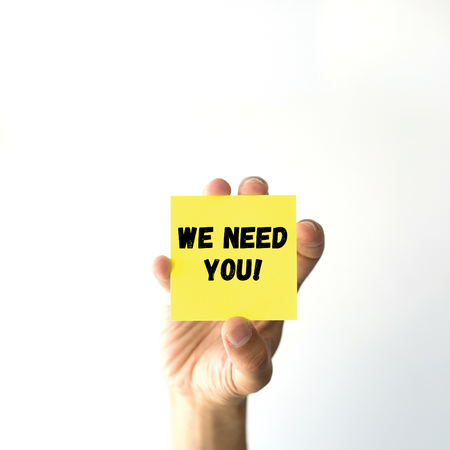 sticky note: Hand holding yellow sticky note written WE NEED YOU! word