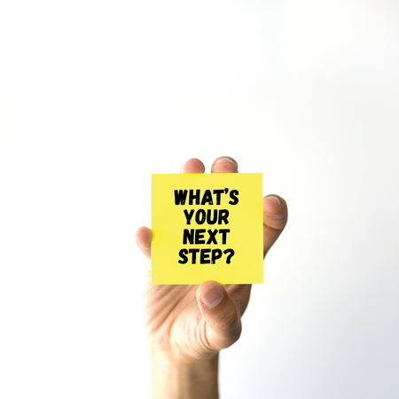 what's ahead: Hand holding yellow sticky note written WHATS YOUR NEXT STEP?