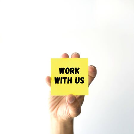 new recruit: Hand holding yellow sticky note written WORK WITH US word