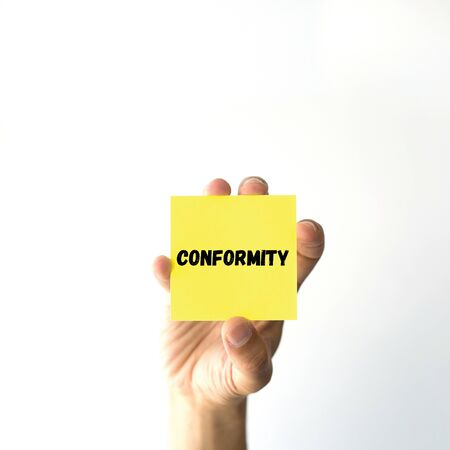 conformity: Hand holding yellow sticky note written CONFORMITY word