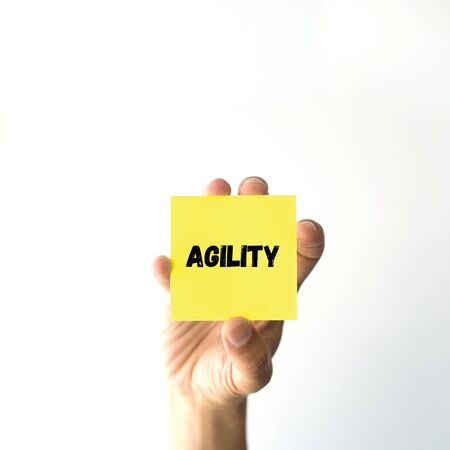 agility: Hand holding yellow sticky note written AGILITY word Stock Photo