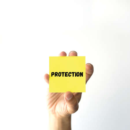 sticky note: Hand holding yellow sticky note written PROTECTION word