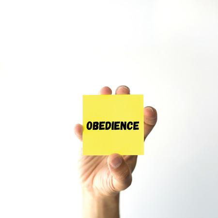 obediencia: Mano que sostiene la nota amarilla pegajosa palabra escrita OBEDIENCIA