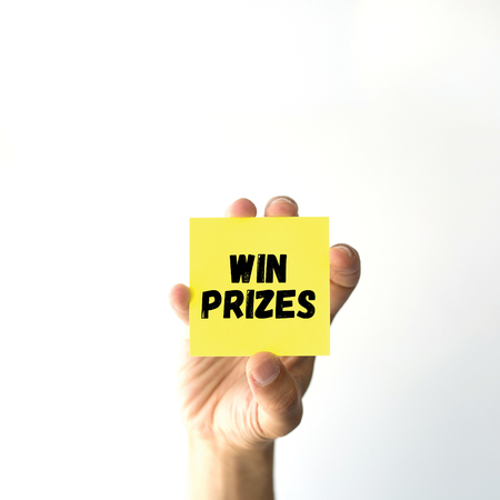 Hand holding yellow sticky note written WIN PRIZES word