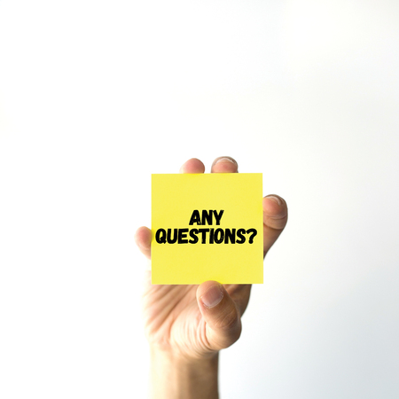 questions: Hand holding yellow sticky note written ANY QUESTIONS? word Stock Photo