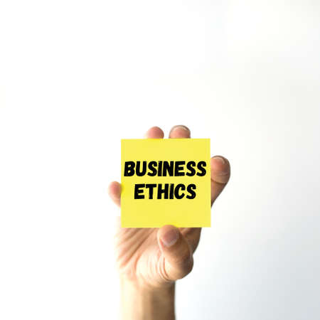 ethic: Hand holding yellow sticky note written BUSINESS ETHICS word