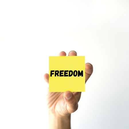 openness: Hand holding yellow sticky note written FREEDOM word Stock Photo