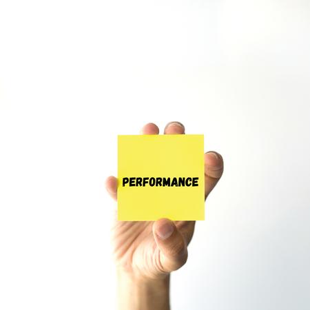 summarized: Hand holding yellow sticky note written PERFORMANCE word Stock Photo