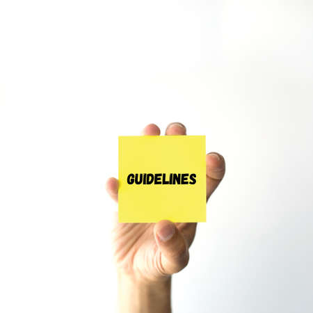 accordance: Hand holding yellow sticky note written GUIDELINES word