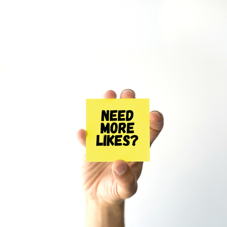likes: Hand holding yellow sticky note written NEED MORE LIKES?