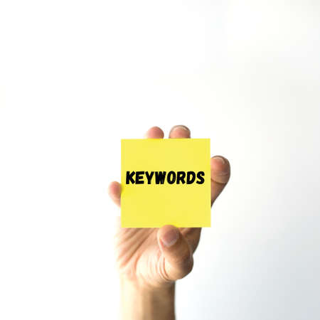 techiques: Hand holding yellow sticky note written KEYWORDS Stock Photo