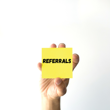 referidos: Hand holding yellow sticky note written REFERRALS