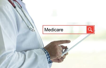 health care provider: DOCTOR USING TABLET PC AND SEARCHING MEDICARE ON WEB Stock Photo