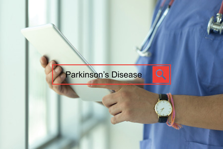 DOCTOR USING TABLET PC SEARCHING PARKINSONS DISEASE