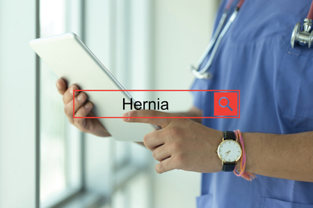 hernia: DOCTOR USING TABLET PC SEARCHING HERNIA Stock Photo
