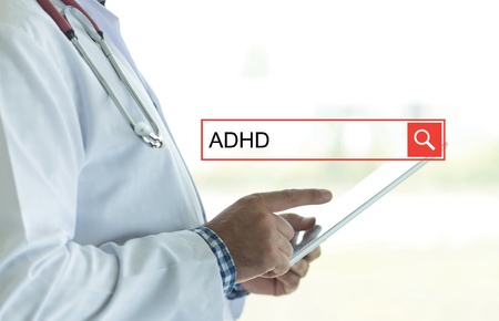 hyperactivity: DOCTOR USING TABLET PC AND SEARCHING ADHD ON WEB Stock Photo