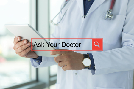 doctor burnout: DOCTOR USING TABLET PC SEARCHING ASK YOUR DOCTOR ON WEB Stock Photo