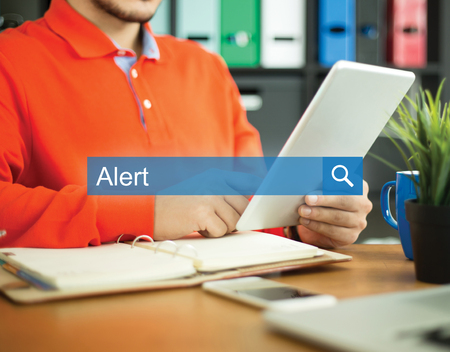 spy ware: Young man working in an office with tablet pc and searching ALERT word on internet Stock Photo