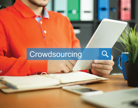 Young man working in an office with tablet pc and searching CROWDSOURCING word on internet