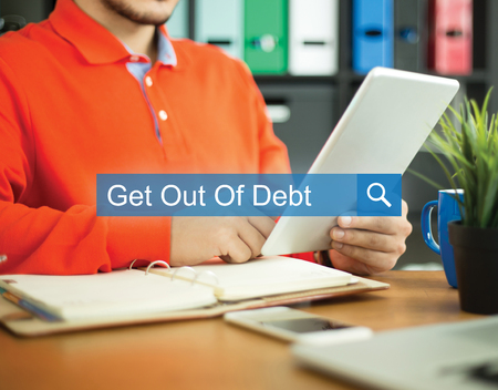 get out: Young man working in an office with tablet pc and searching GET OUT OF DEBT word on internet