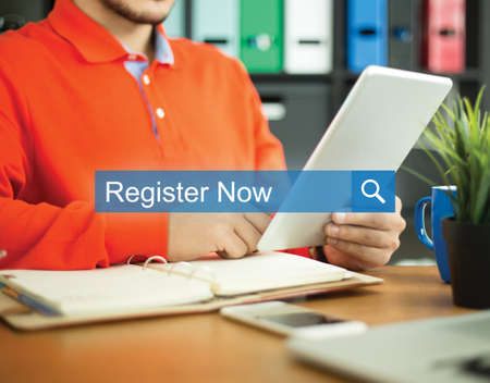 Young man working in an office with tablet pc and searching REGISTER NOW word on internet Stock Photo