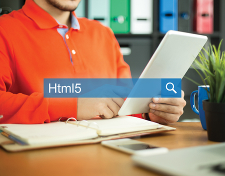Young man working in an office with tablet pc and searching HTML5 word on internet Stock Photo