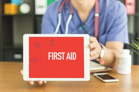 Young and professional medical doctor showing a tablet pc and FIRST AID concept on screen