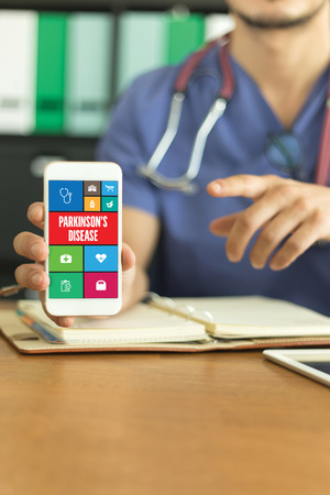 parkinson's disease: Young and professional medical doctor showing a smartphone and PARKINSONS DISEASE concept on screen Stock Photo