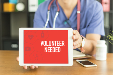 non profit: Young and professional medical doctor showing a tablet pc and VOLUNTEER NEEDED concept on screen Stock Photo