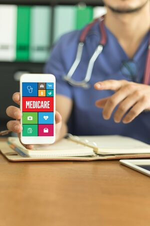 health care provider: Young and professional medical doctor showing a smartphone and MEDICARE concept on screen Stock Photo