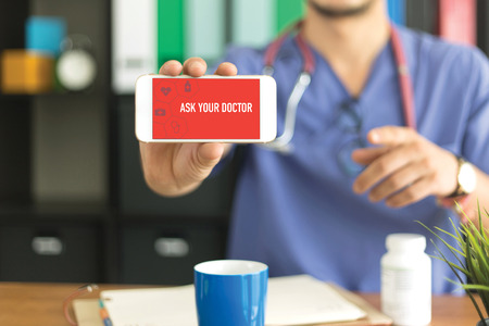 doctor burnout: Young and professional medical doctor showing a smartphone and ASK YOUR DOCTOR concept on screen Stock Photo