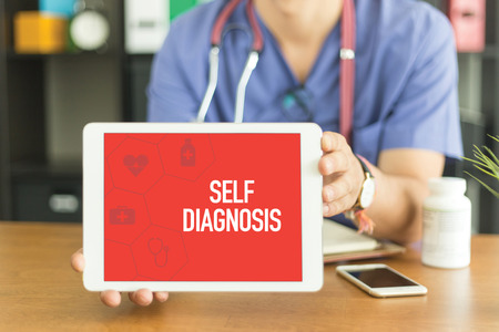 assessment system: Young and professional medical doctor showing a tablet pc and SELF DIAGNOSIS concept on screen Stock Photo
