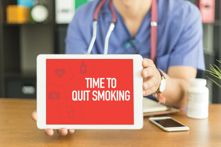 Young and professional medical doctor showing a tablet pc and TIME TO QUIT SMOKING concept on screen Stock Photo