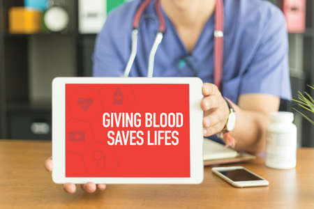 donacion de organos: Young and professional medical doctor showing a tablet pc and GIVING BLOOD SAVES LIFES concept on screen Foto de archivo