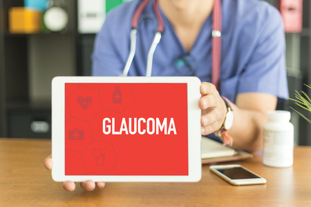 Young and professional medical doctor showing a tablet pc and GLAUCOMA concept on screen Stock Photo