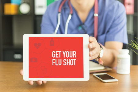 Young and professional medical doctor showing a tablet pc and GET YOUR FLU SHOT concept on screen