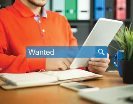 recruit help: Young man working in an office with tablet pc and searching WANTED word on internet Stock Photo